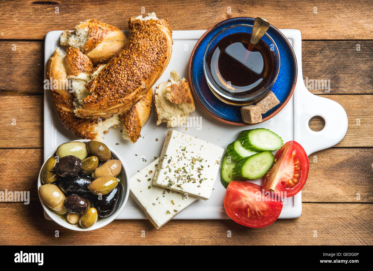 Turkish traditional breakfast with feta cheese, vegetables, olives, simit bagel and black tea on white ceramic board - Stock Image