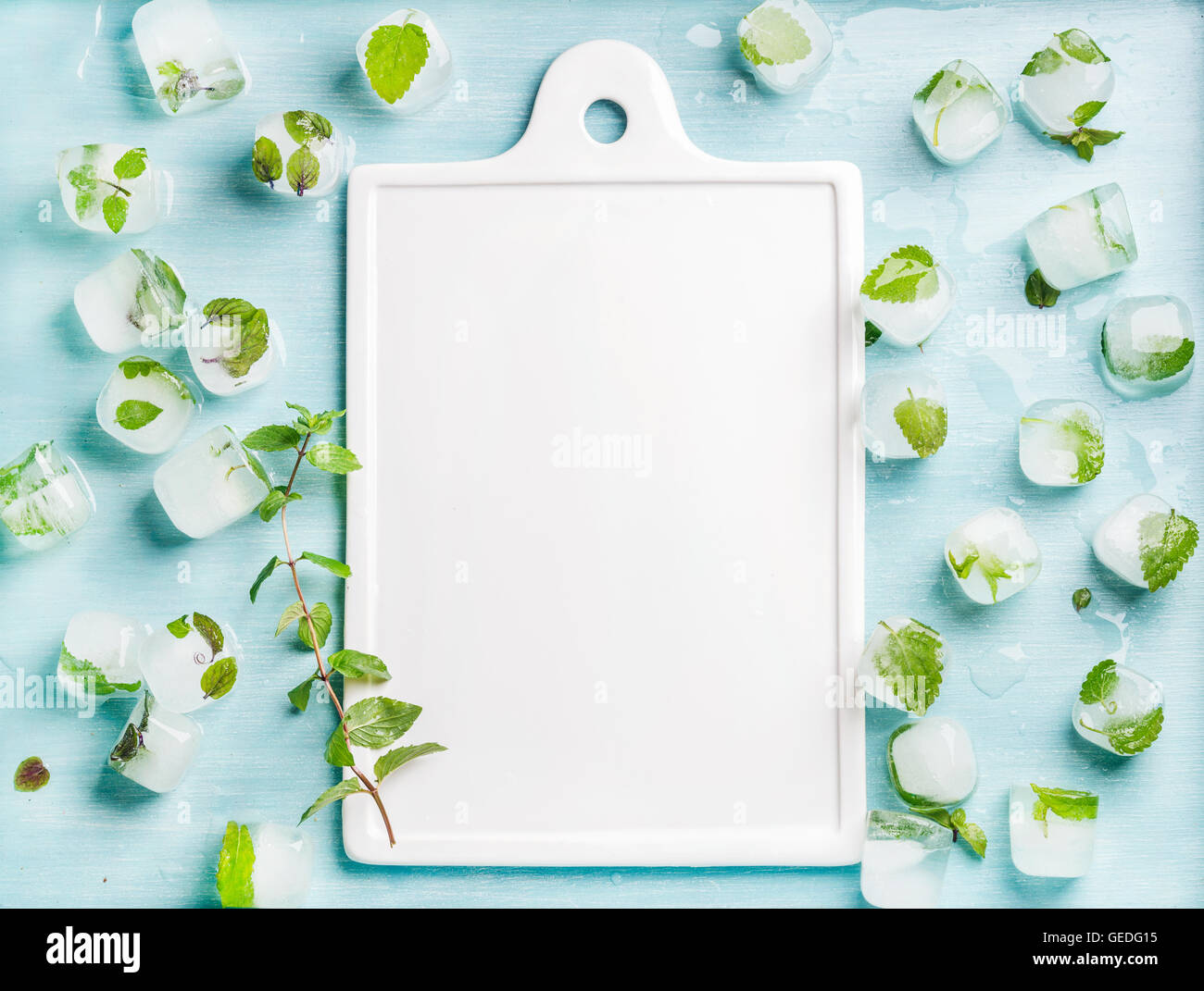 Ice cubes with frozen mint leaves inside on blue Turquoise background and white ceramic board in center, copy space - Stock Image