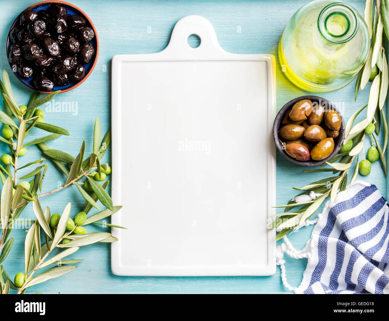 Two bowls with pickled green and black olives, olive tree sprigs, oil in glass bottle, white ceramic board in center - Stock Image