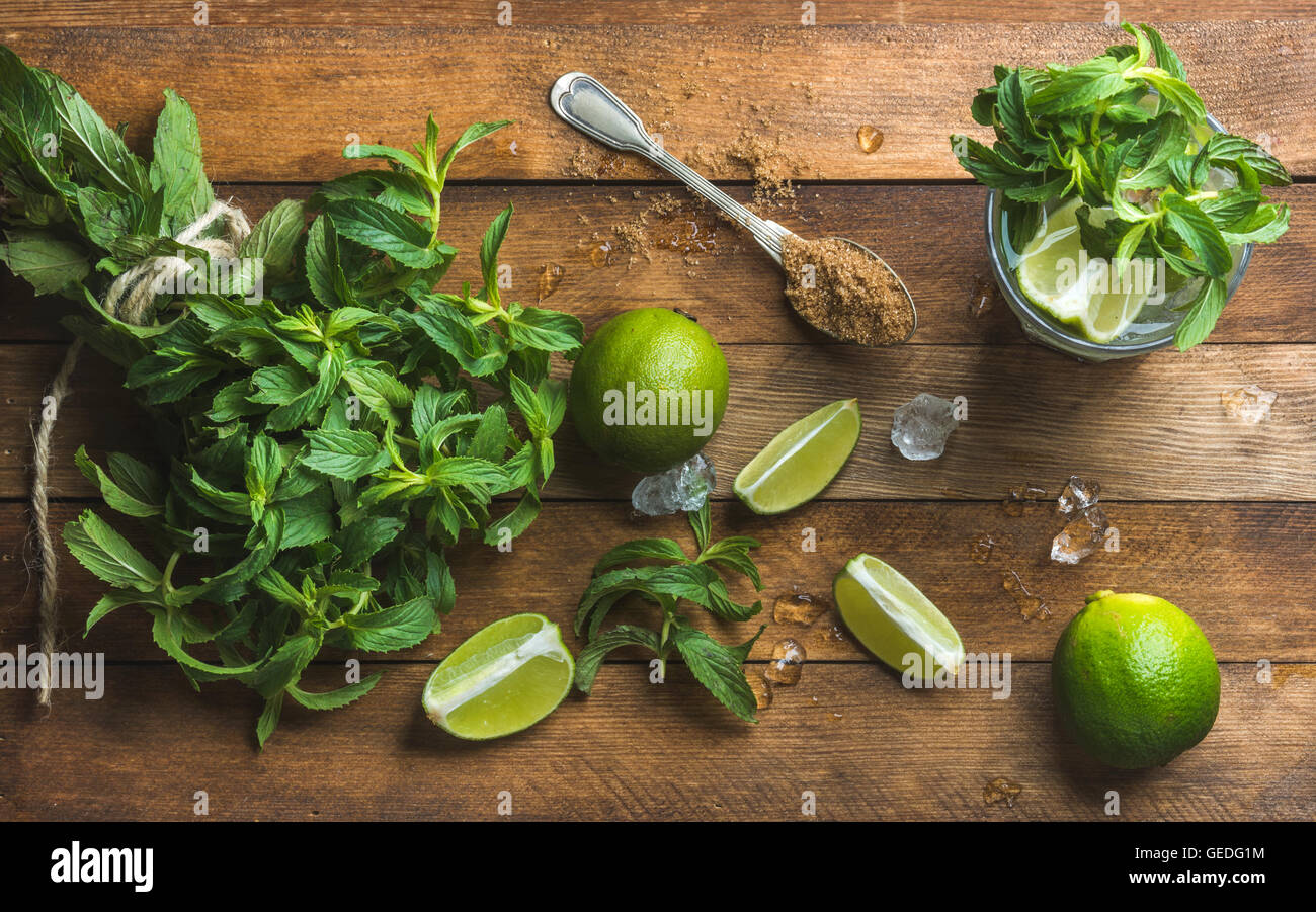 Ingredients for making mojito summer cocktail. Fresh mint bunch and leaves, limes, spoon of brown sugar, ice over - Stock Image