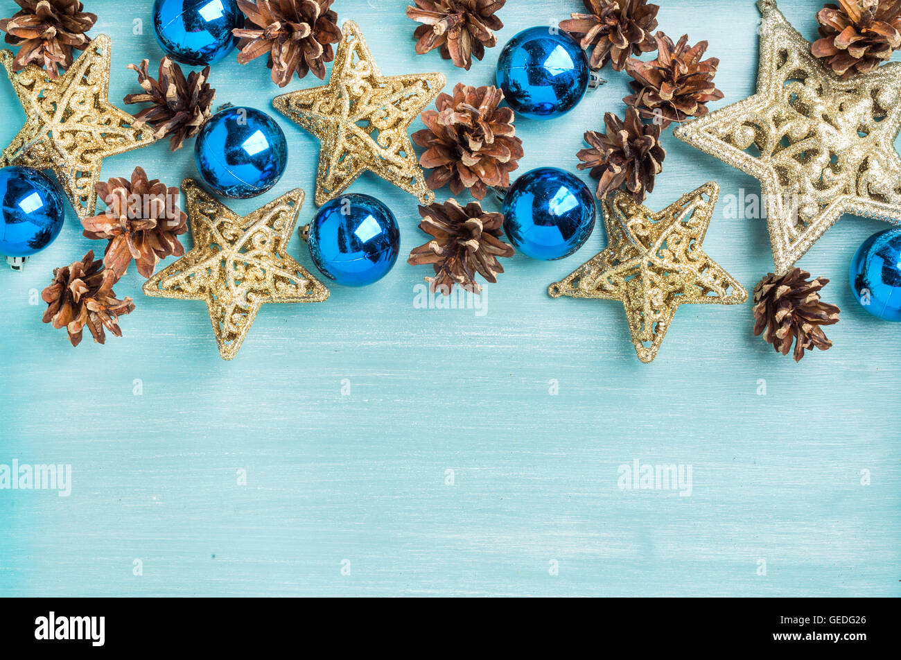 Christmas or new year decoration background: pine cones, blue glass balls, golden stars on painted backdrop, copy - Stock Image
