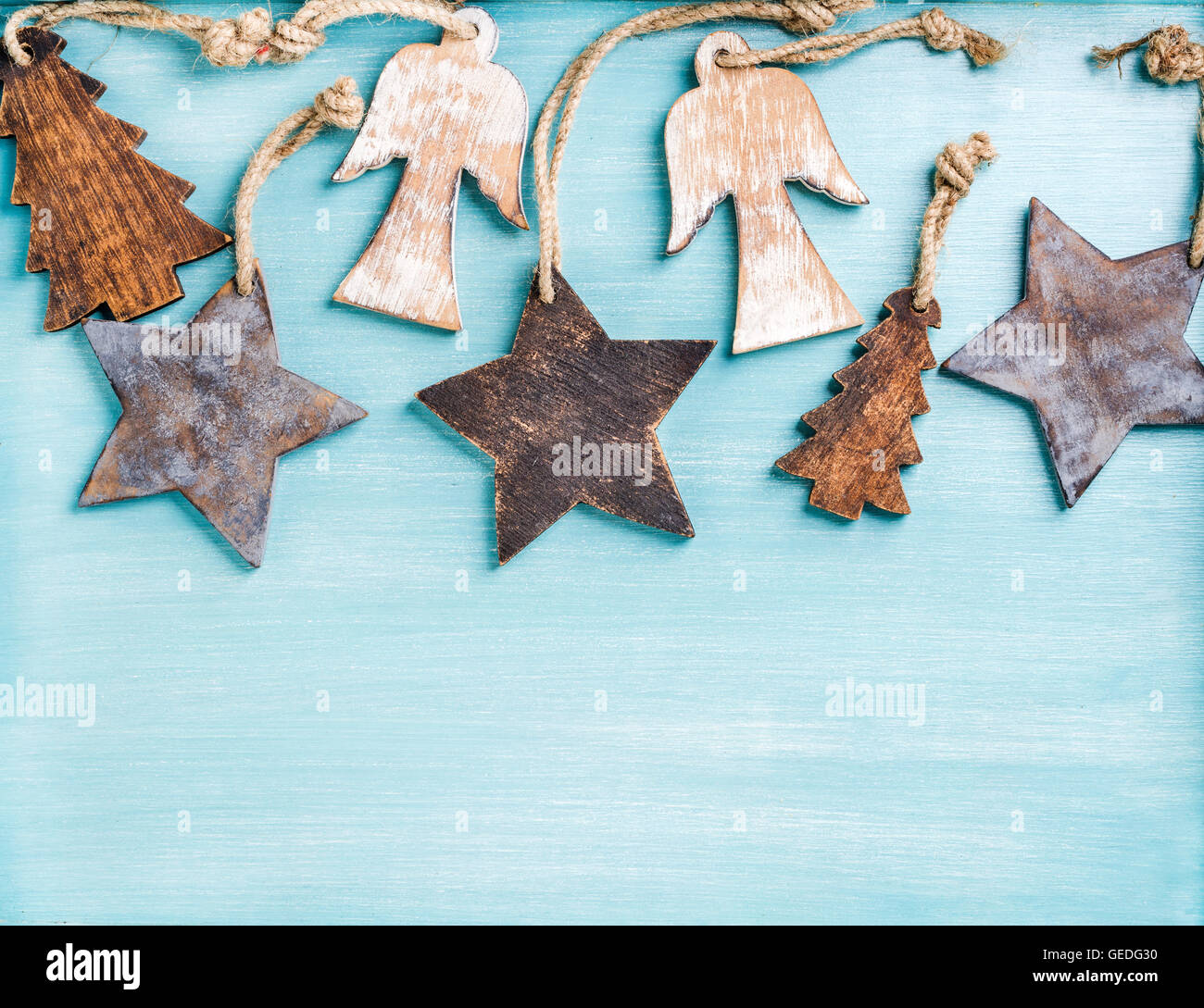 New Year or Christmas background: wooden angels, stars and small fir-trees over blue painted  backdrop, copy space - Stock Image