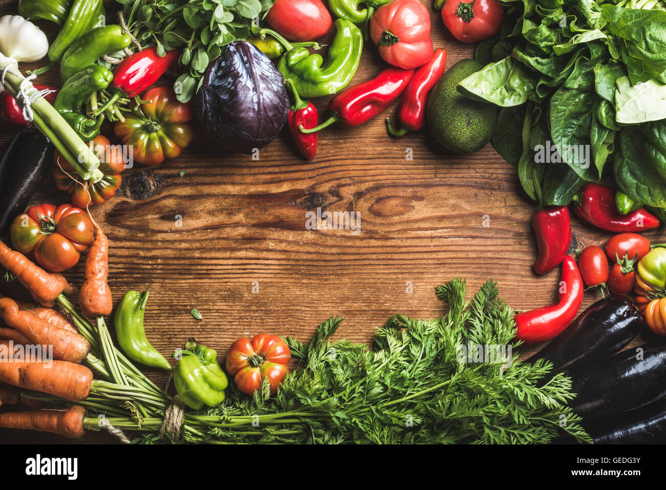 Fresh raw vegetable ingredients for healthy cooking or salad making over rustic wood background, top view, copy - Stock Image