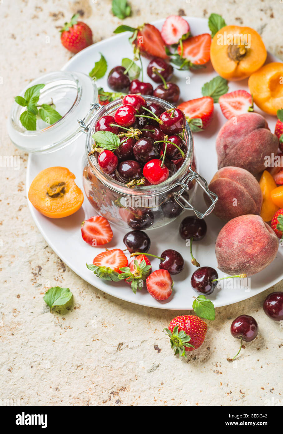 Healthy summer fruit variety. Sweet cherries in glass jar, strawberries, peaches, apricots and mint leaves on white - Stock Image