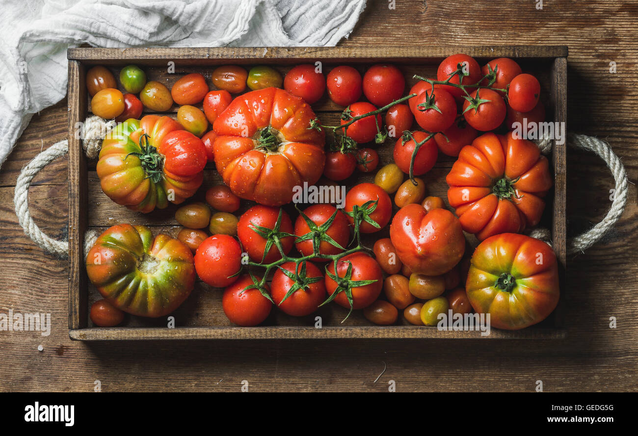 Colorful assortment of heirloom, bunch and cherry tomatoes in rustic tray over wooden background - Stock Image