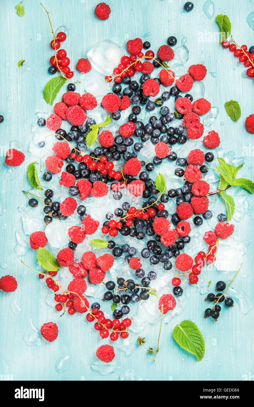 Fresh summer garden berry variety. Rasberry, black and red currant, bilberrry, mint on crushed ice over blue background Stock Photo
