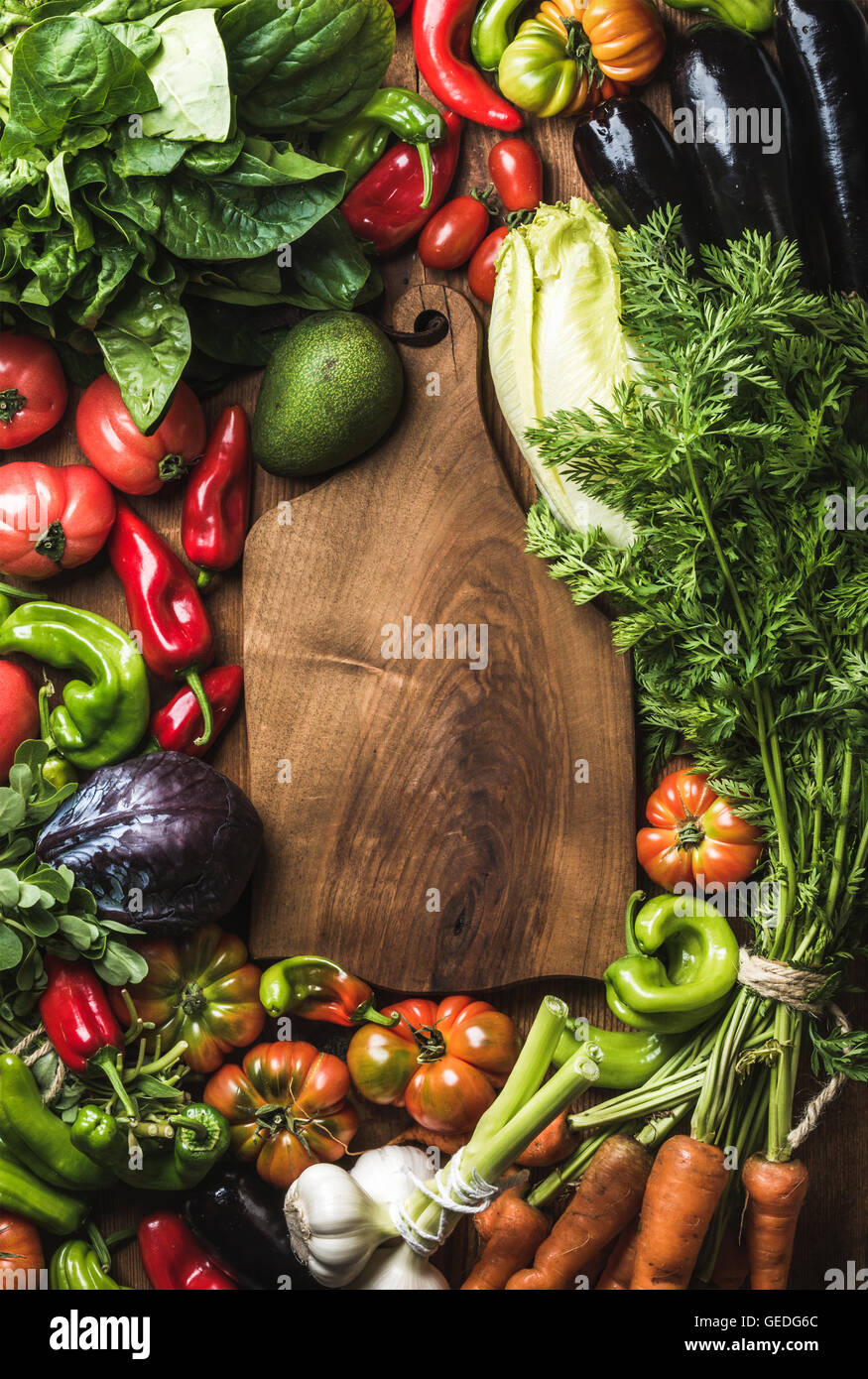 Fresh raw vegetable ingredients for healthy cooking or salad making with rustic wood board in center, top view, - Stock Image