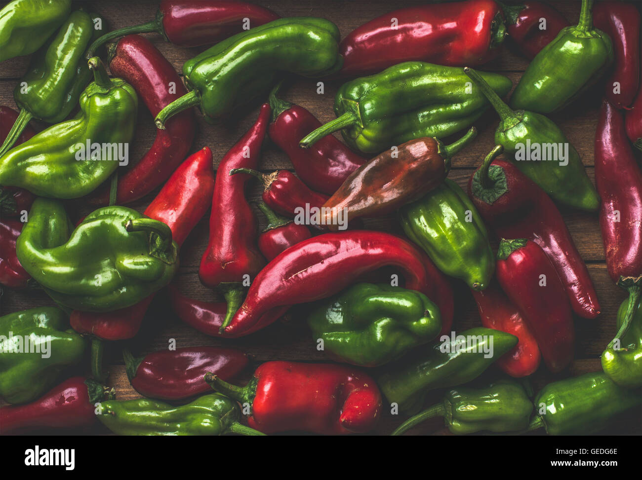 Background of colorful red and green bell peppers over wooden backdrop - Stock Image