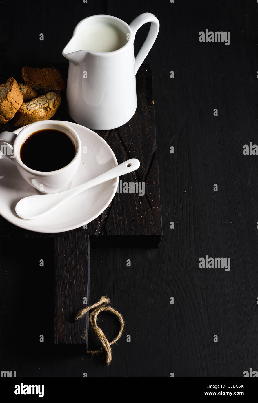 Cup of hot espresso, creamer with milk and cookies on dark rustic wooden board over black background, copy space - Stock Image