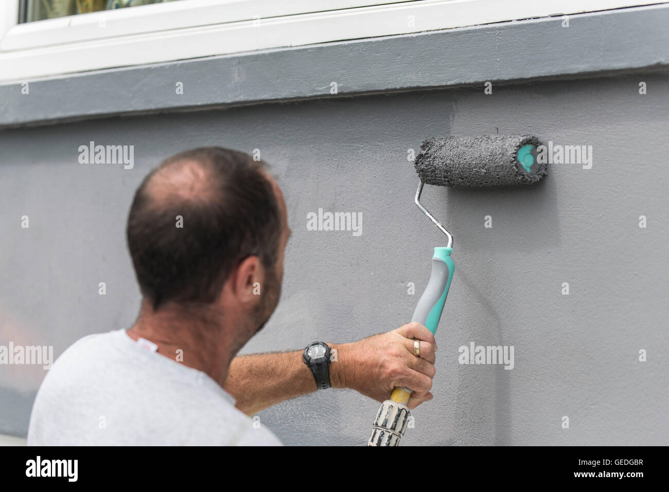 A painter and decorator painting the exterior wall of a house with a roller. - Stock Image
