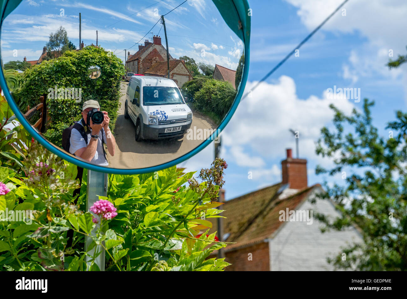 Photographer taking a selfy from a street round mirror of a typical Norfolk village lane. - Stock Image