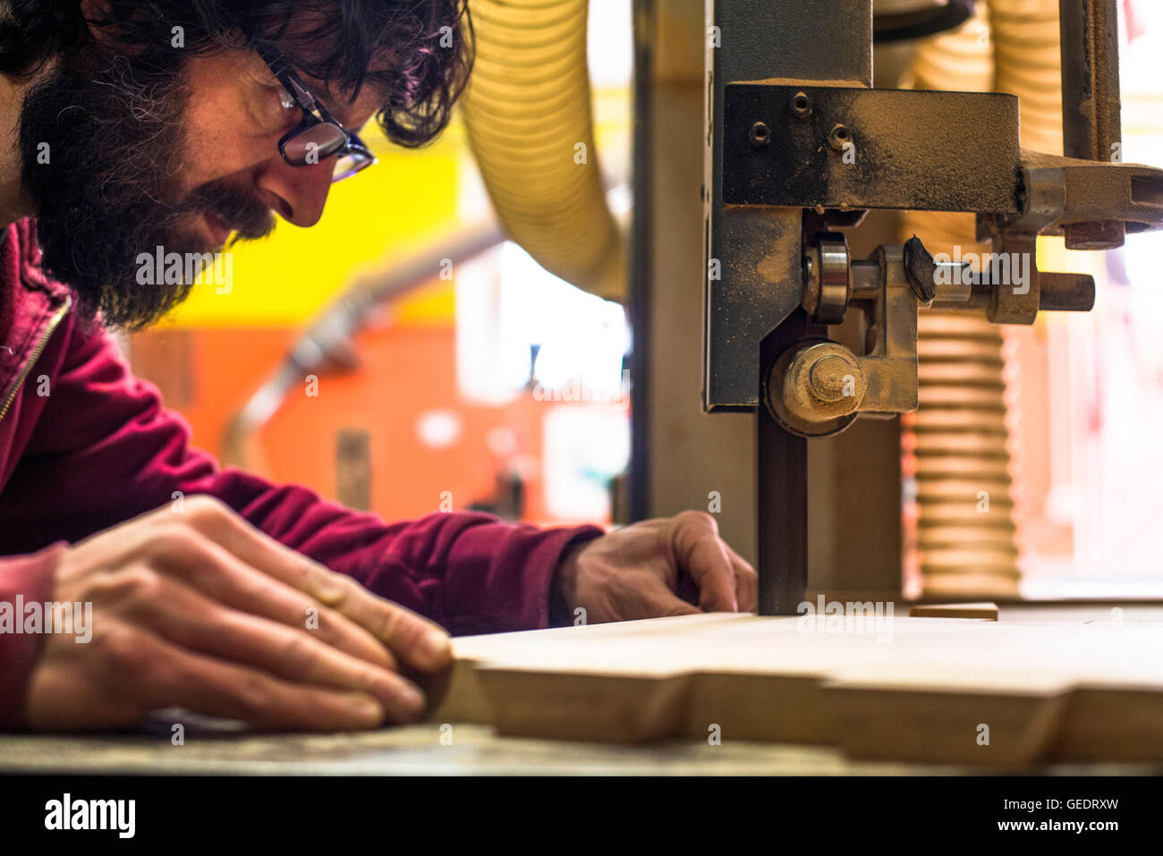 Woodworker Cutting Wood with Band saw Stock Photo