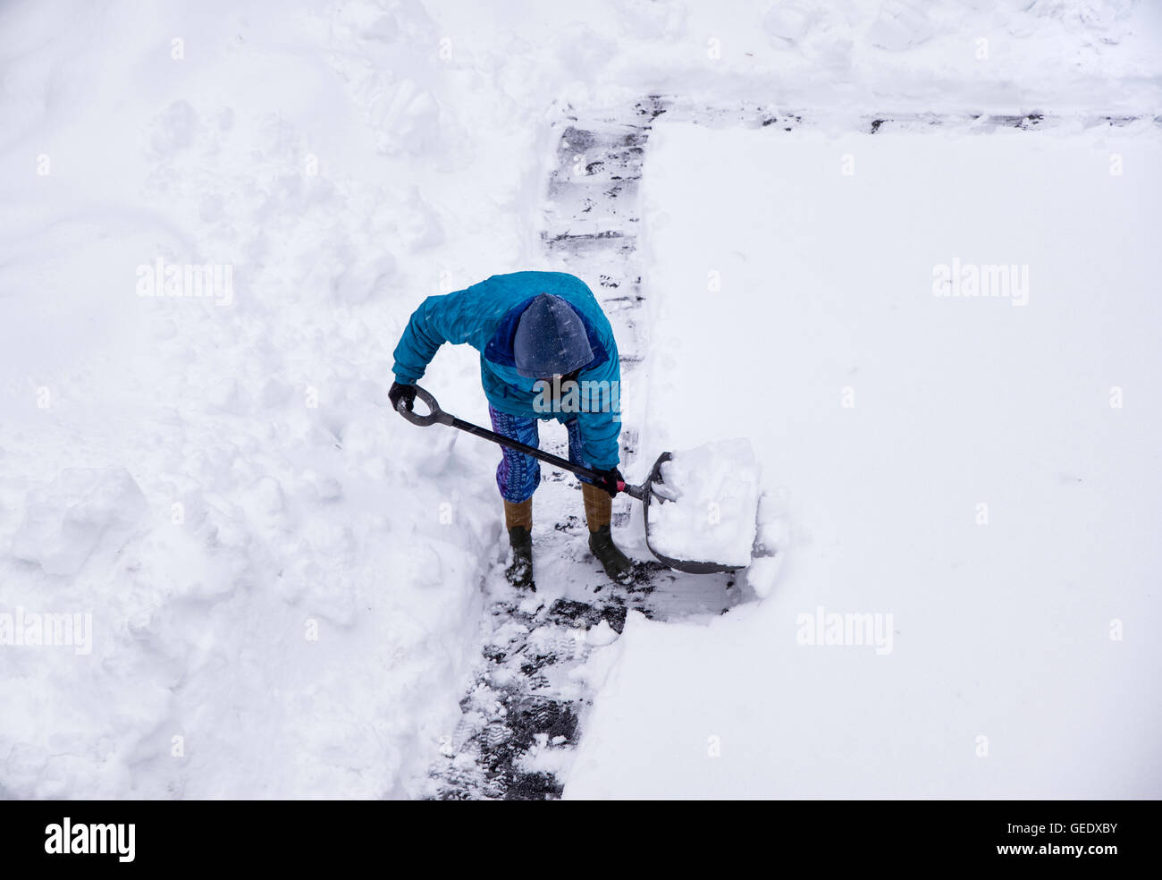 Adult shoveling snow after winter storm. - Stock Image