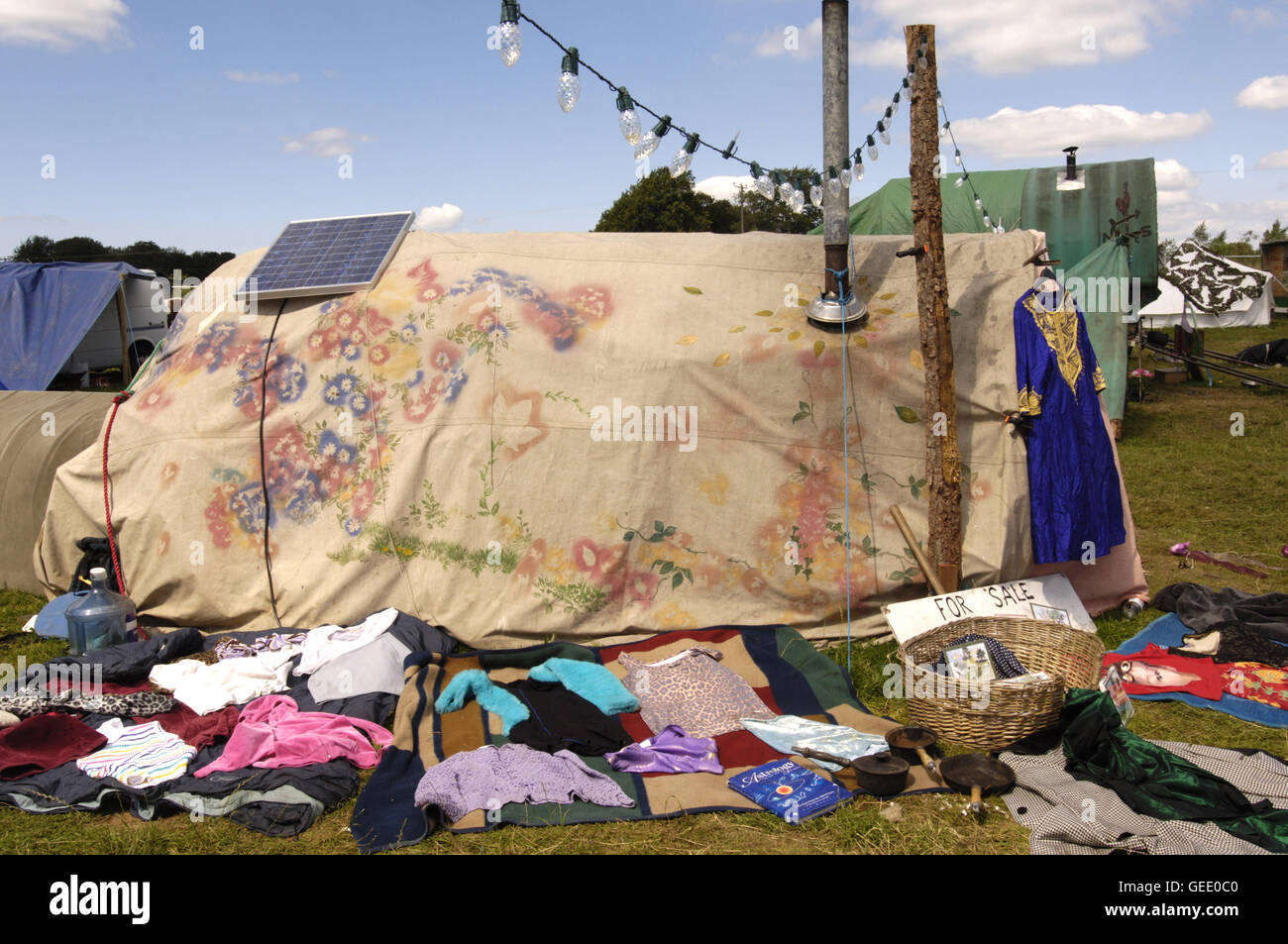 Environmentally conscious festaival goers sell their goods around their solar powered temporary home, Big Green - Stock Image