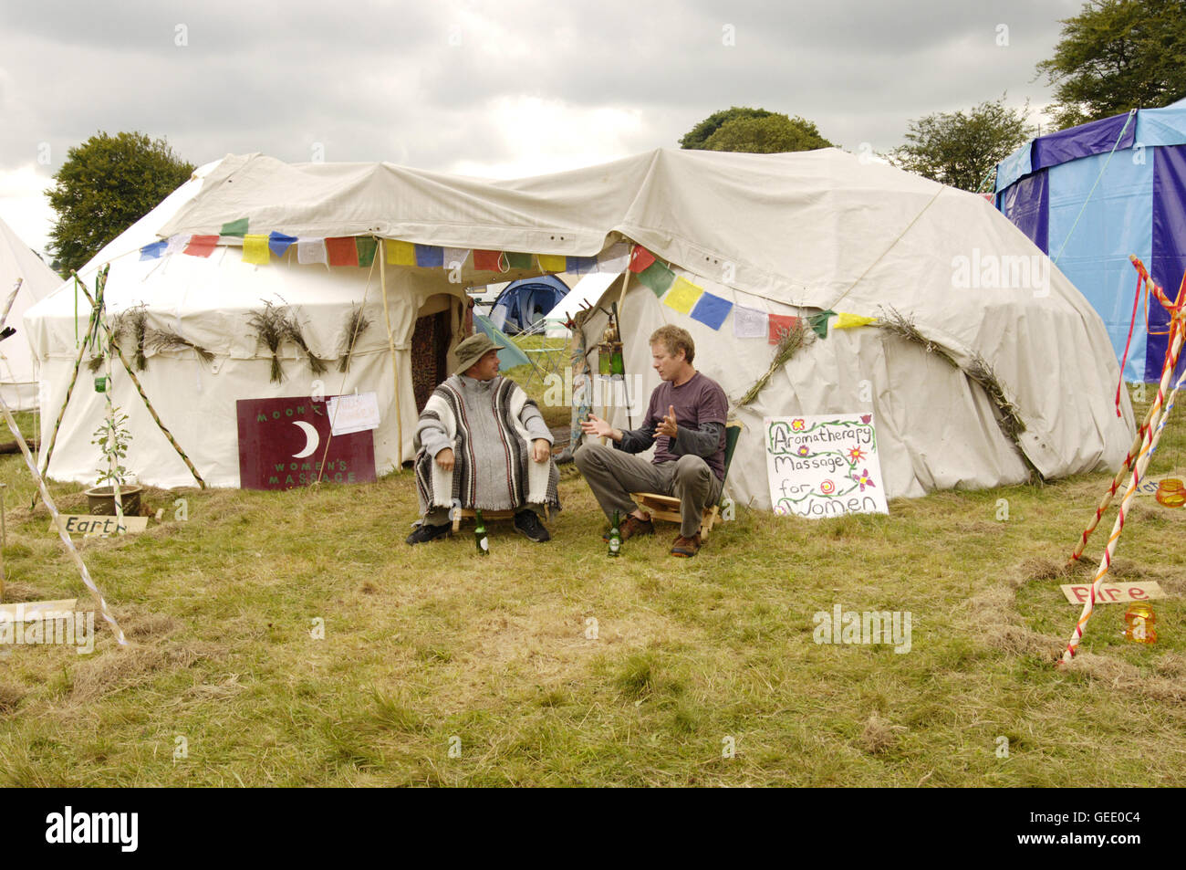 Two Masseurs share a conversation and a beer, Big Green Gathering, UK August 2005 Stock Photo