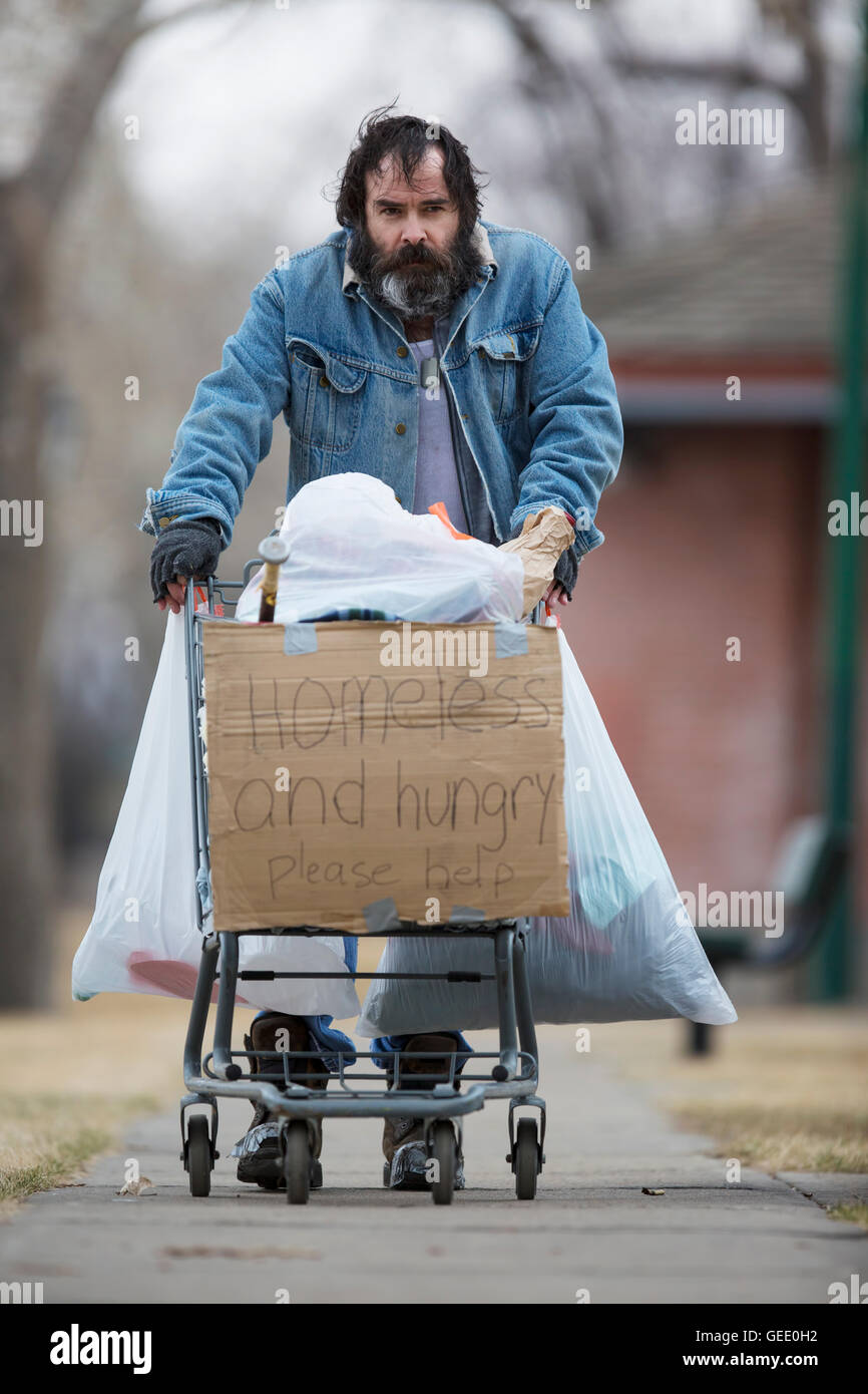 Homeless man with beard pushing a shopping cart with all his possessions. - Stock Image