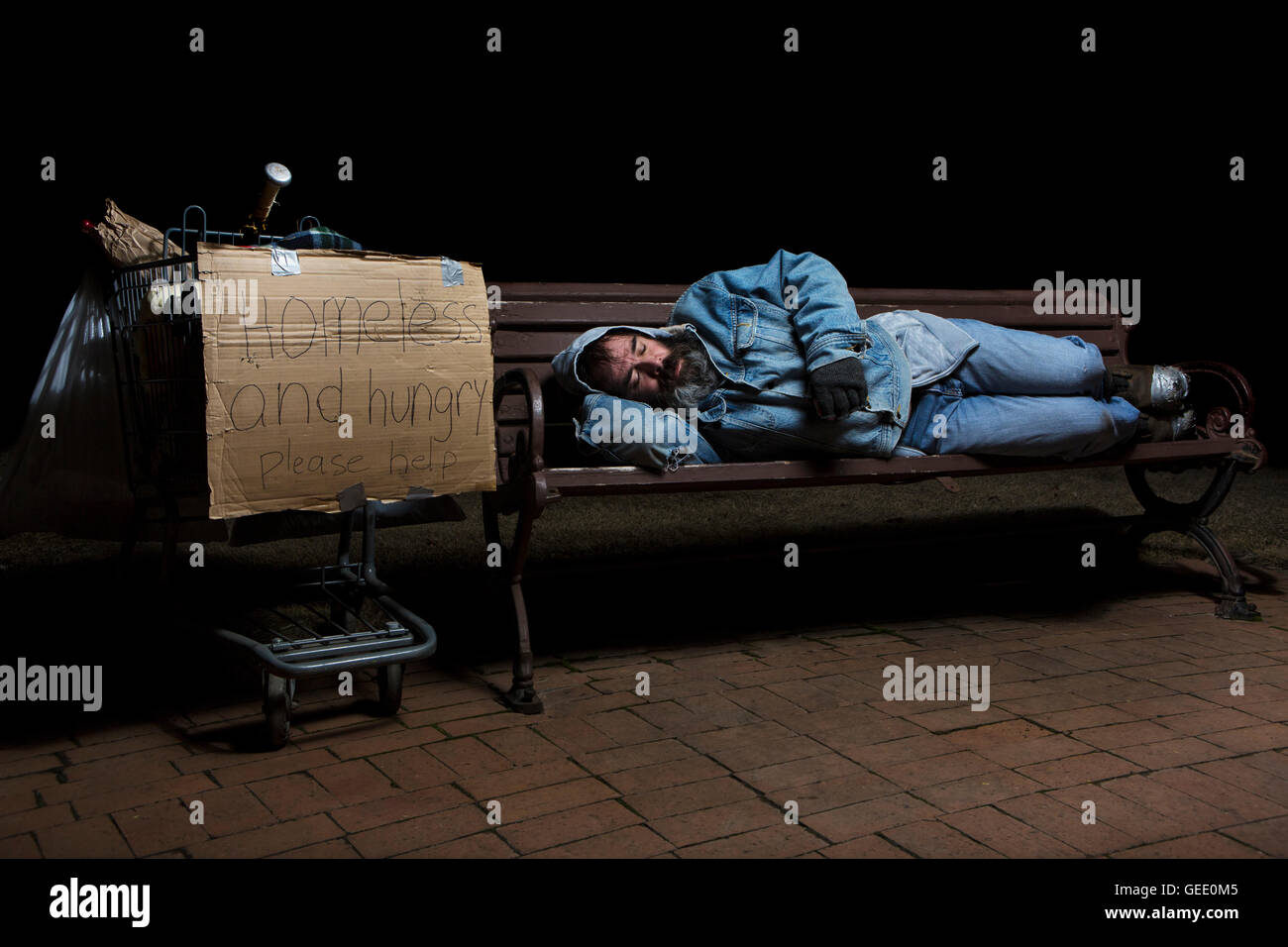 Homeless Man At Night Sleeping On A Park Bench With His Shopping