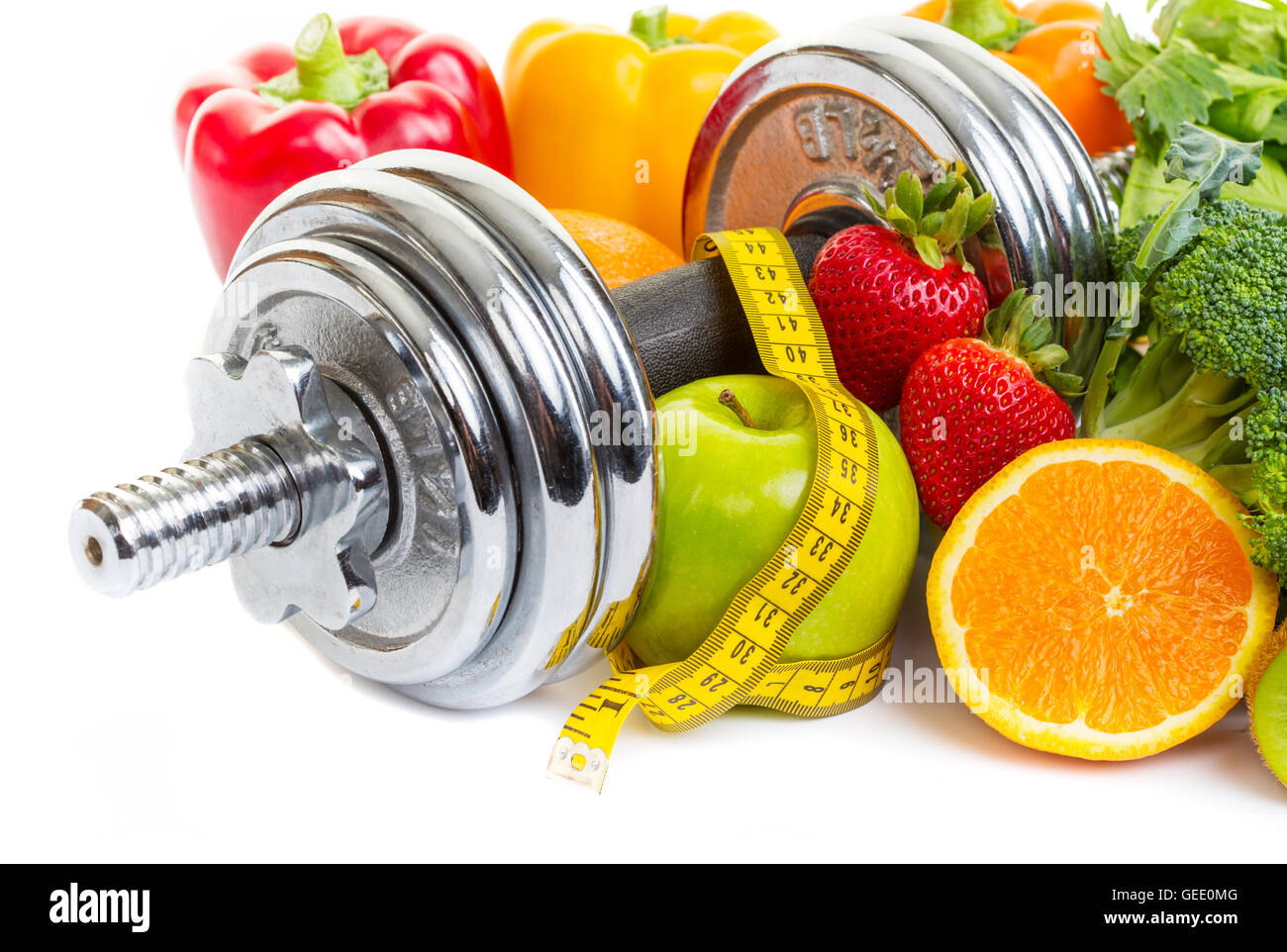 Chrome dumbbells surrounded with healthy fruits and vegetables on a white background. - Stock Image