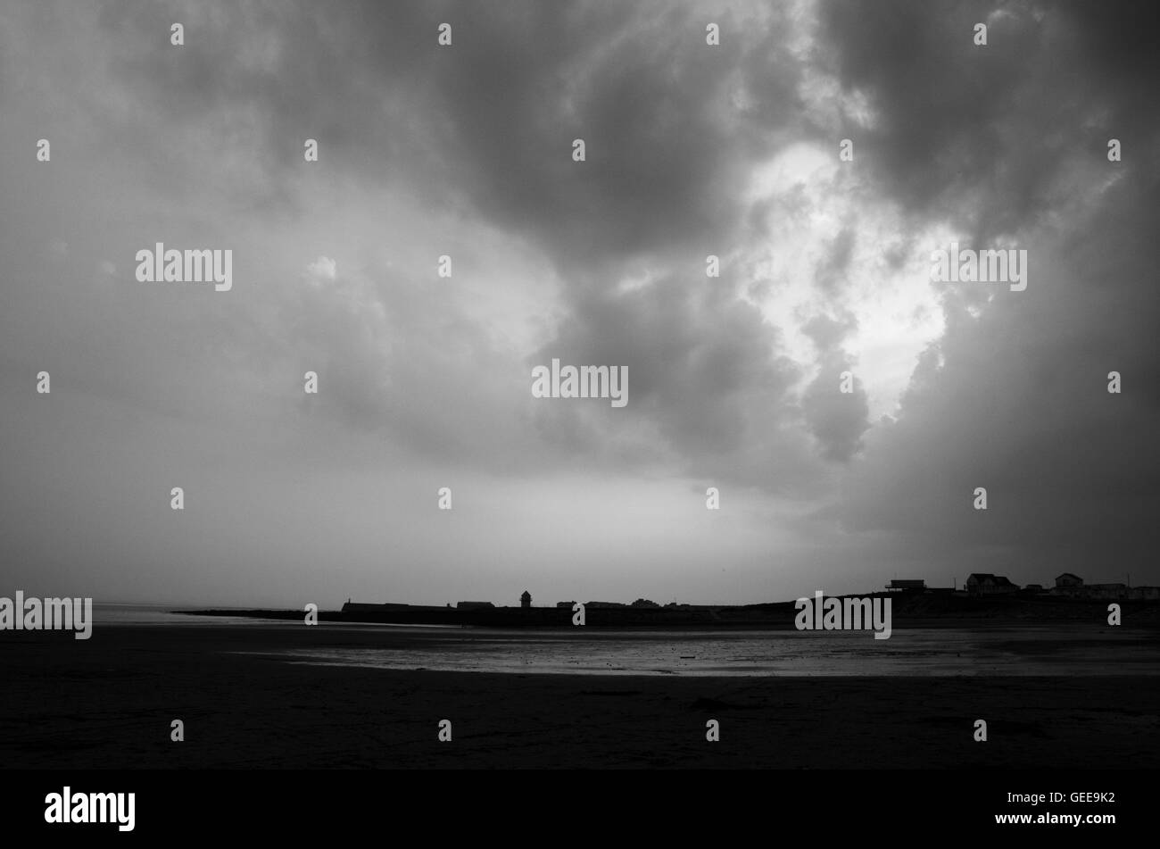 Landscape orientation of Monochrome image showing break in clouds at Trecco Bay - Stock Image