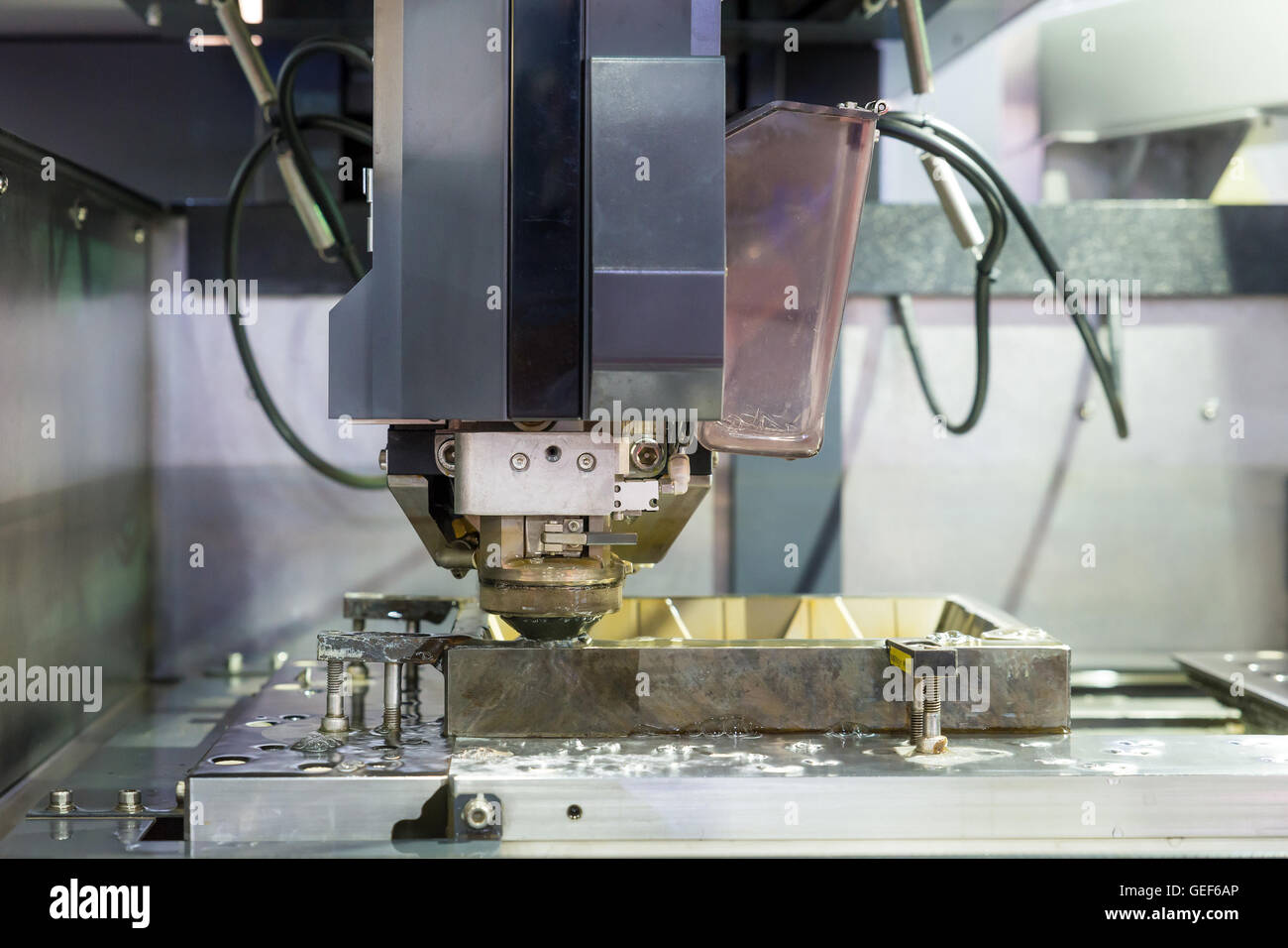 Industrial machine - EDM Industrial machine working with coolant injection in factory. Close up at Industrial machine. - Stock Image