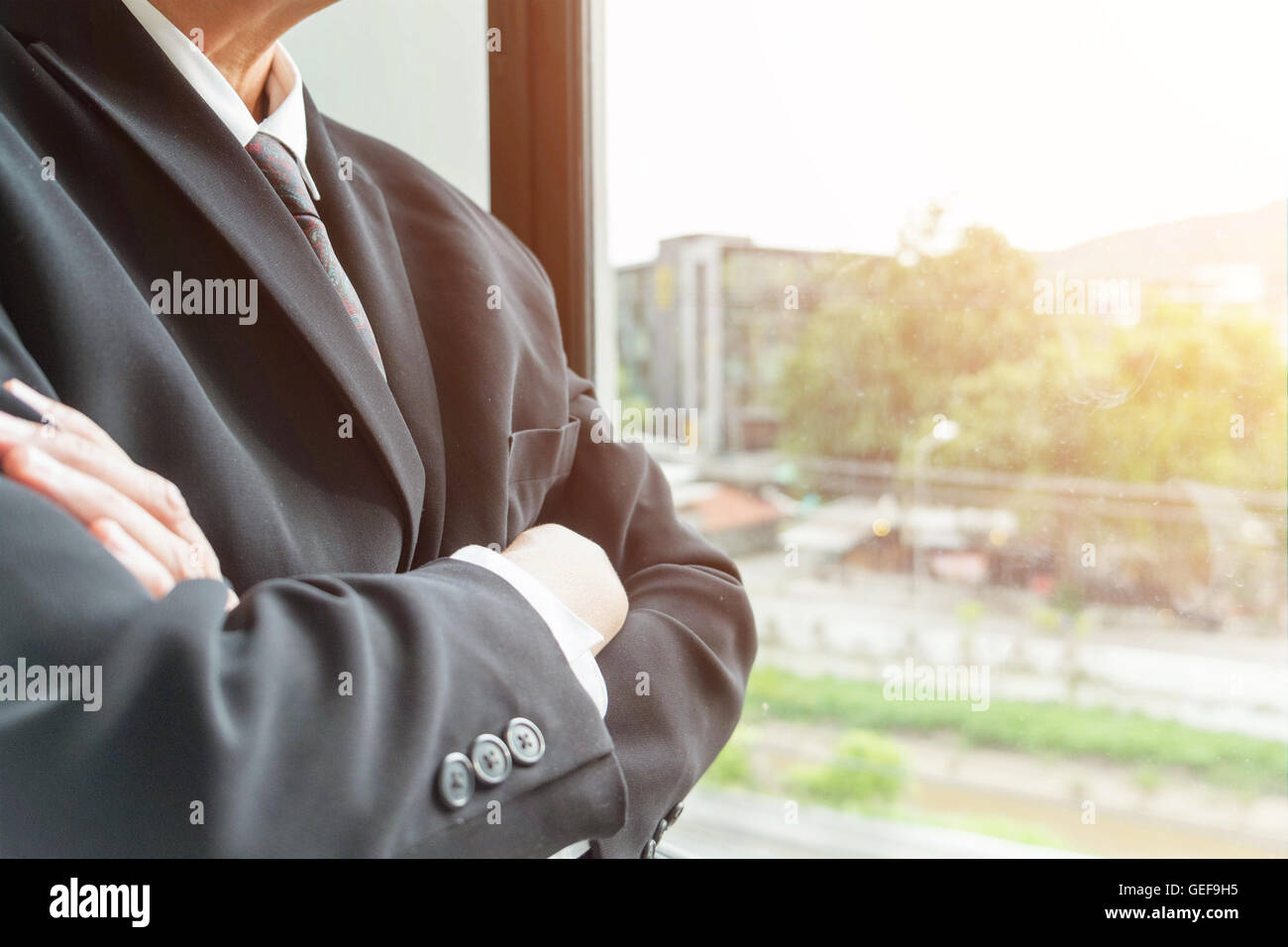 businessman in suit with arms folded looking and think vision of business in office, business concept, soft focus, - Stock Image