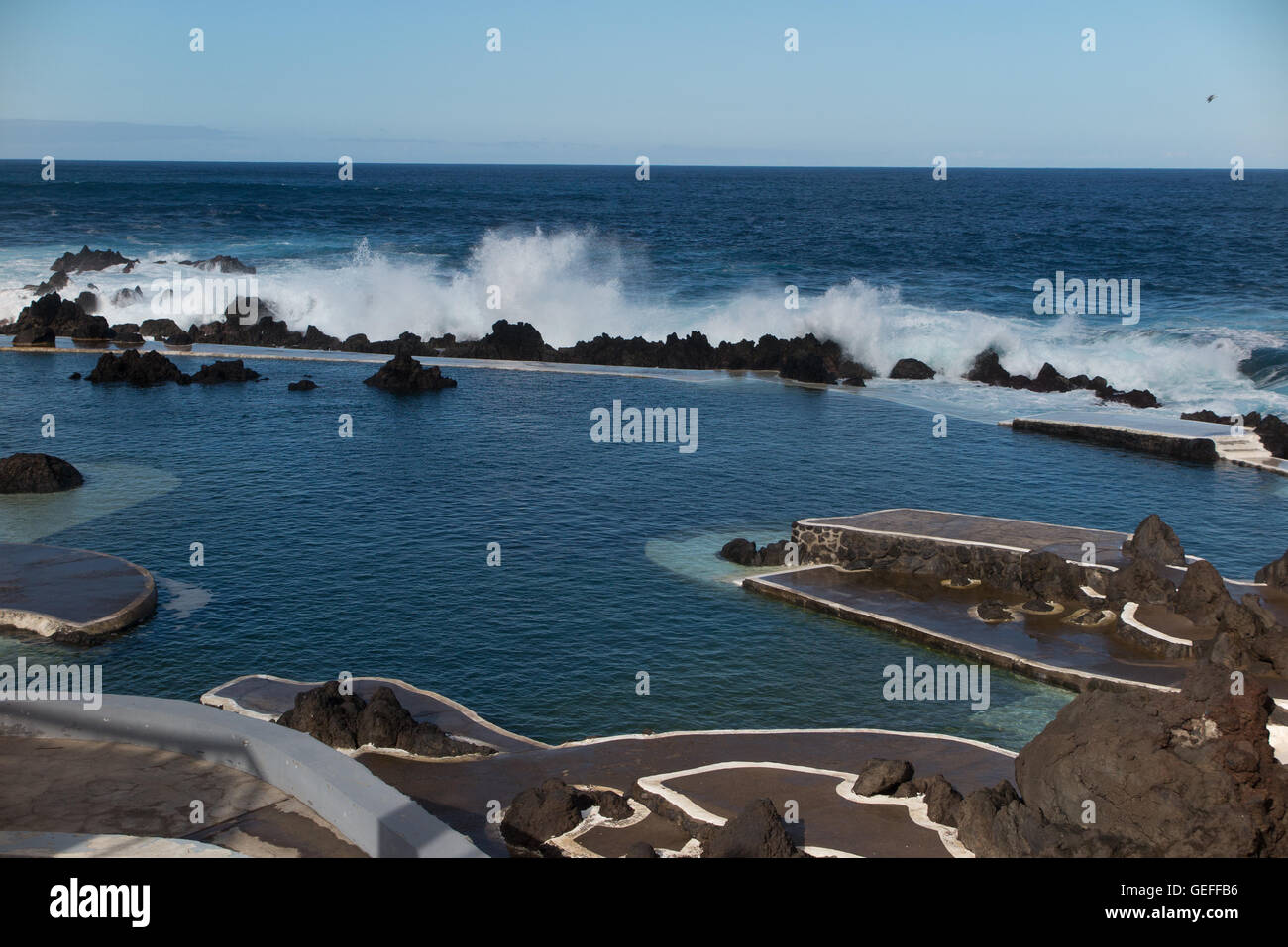 Natural salt water swimming pool formed in the volcanic rocks at Porto Moniz on the north west corner of the island - Stock Image