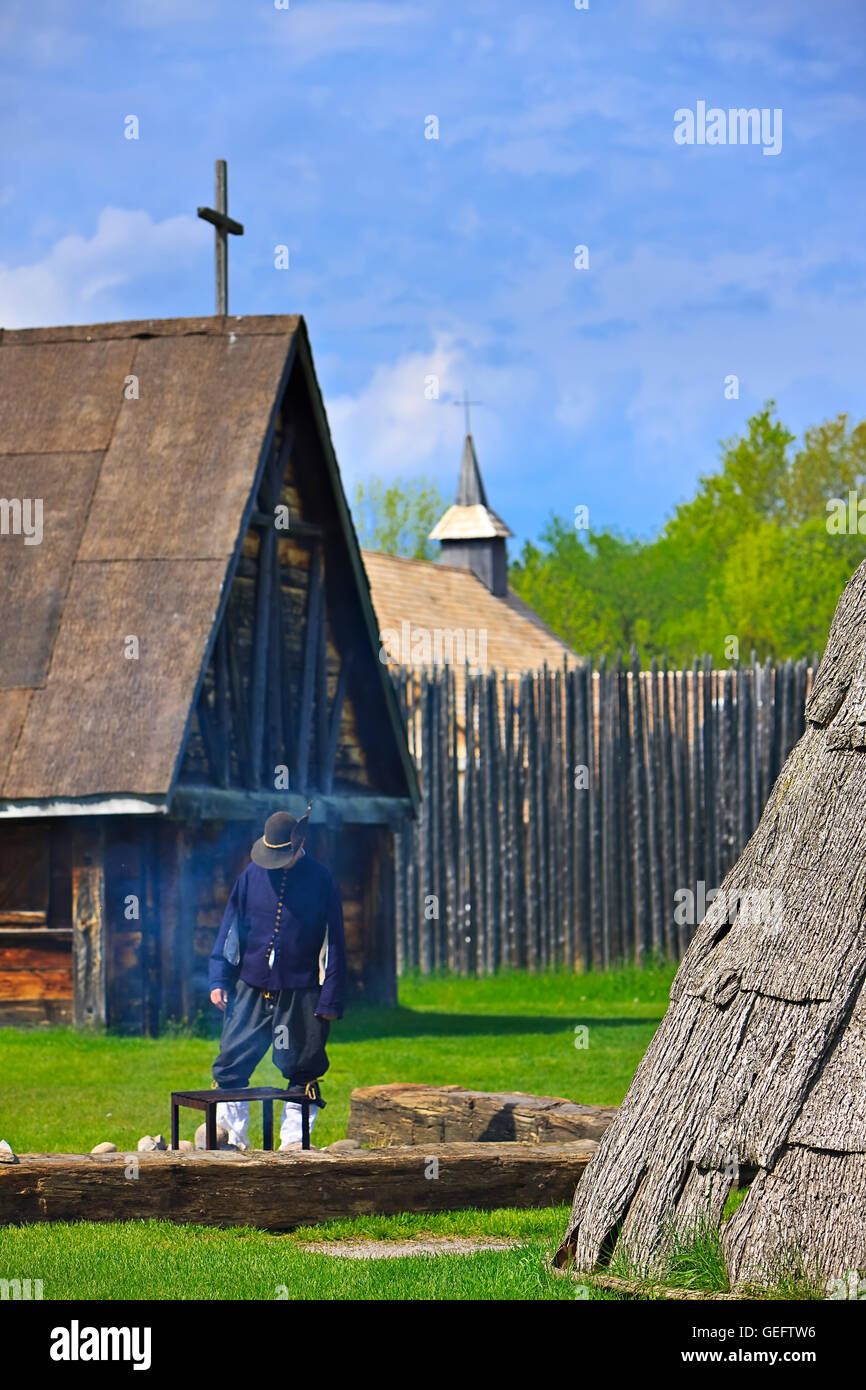 geography,travel,Canada,Ontario,Midland,Costumed character tending a fire in Native Area Sainte-Marie among Hurons - Stock Image