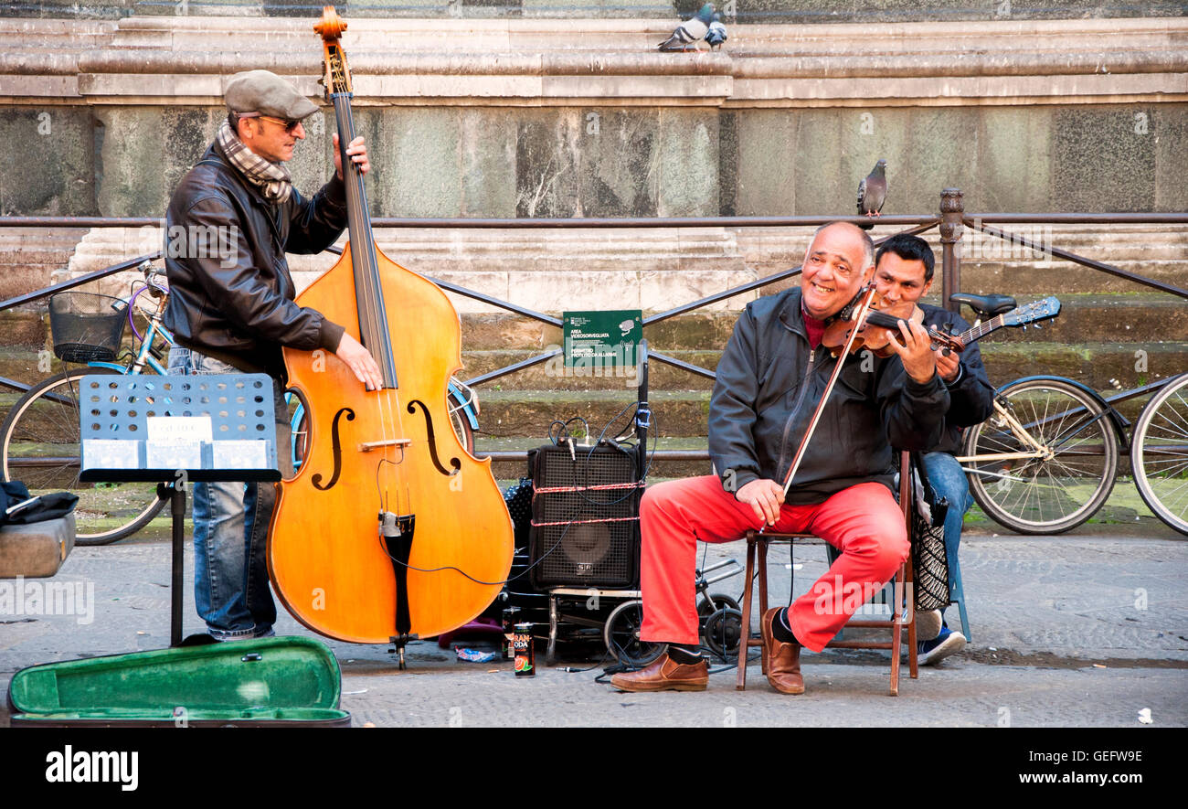 Three street musicians playing on the street of Florence, Italy. Jazz improvisation and string instruments. - Stock Image