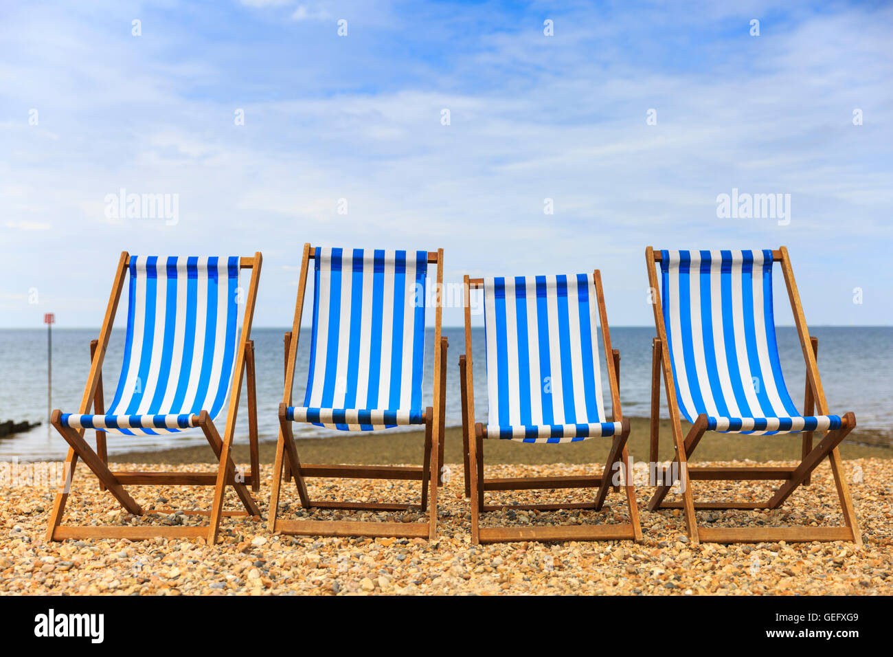 Row of four empty deck chairs on a pebble beach on the sunny seaside in Kent UK  sc 1 st  Alamy & Row of four empty deck chairs on a pebble beach on the sunny seaside ...