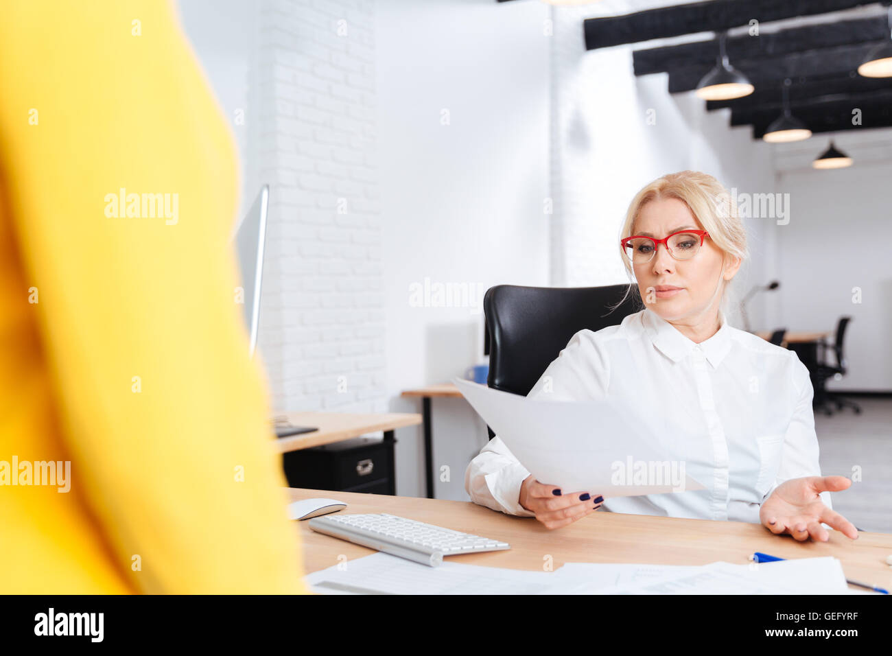 Cheerful beautiful mature businesswoman interviewing candidate for new position in office - Stock Image