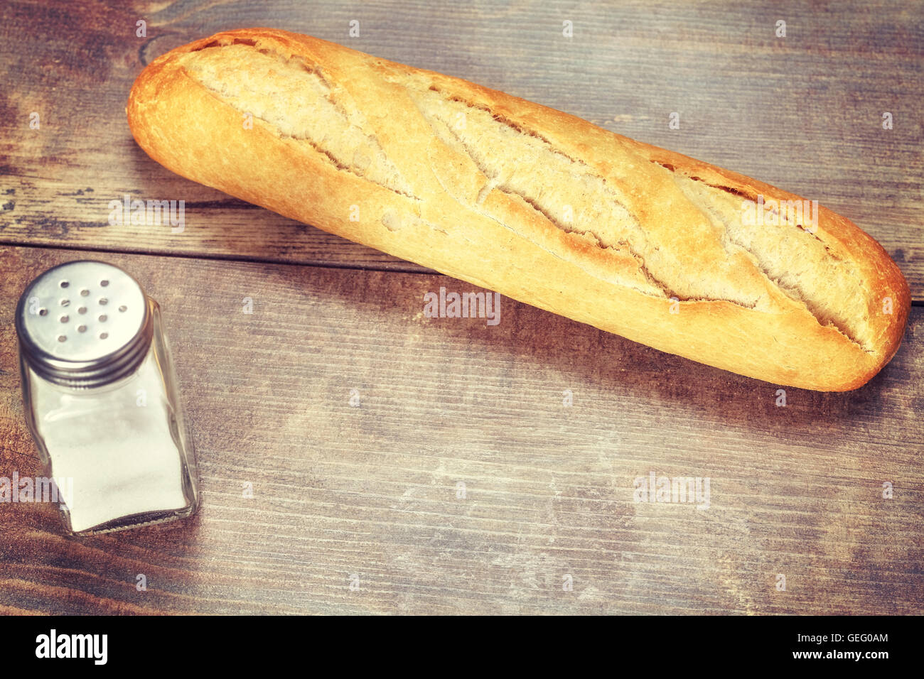 Vintage toned fresh baguette on wooden table, close up - Stock Image