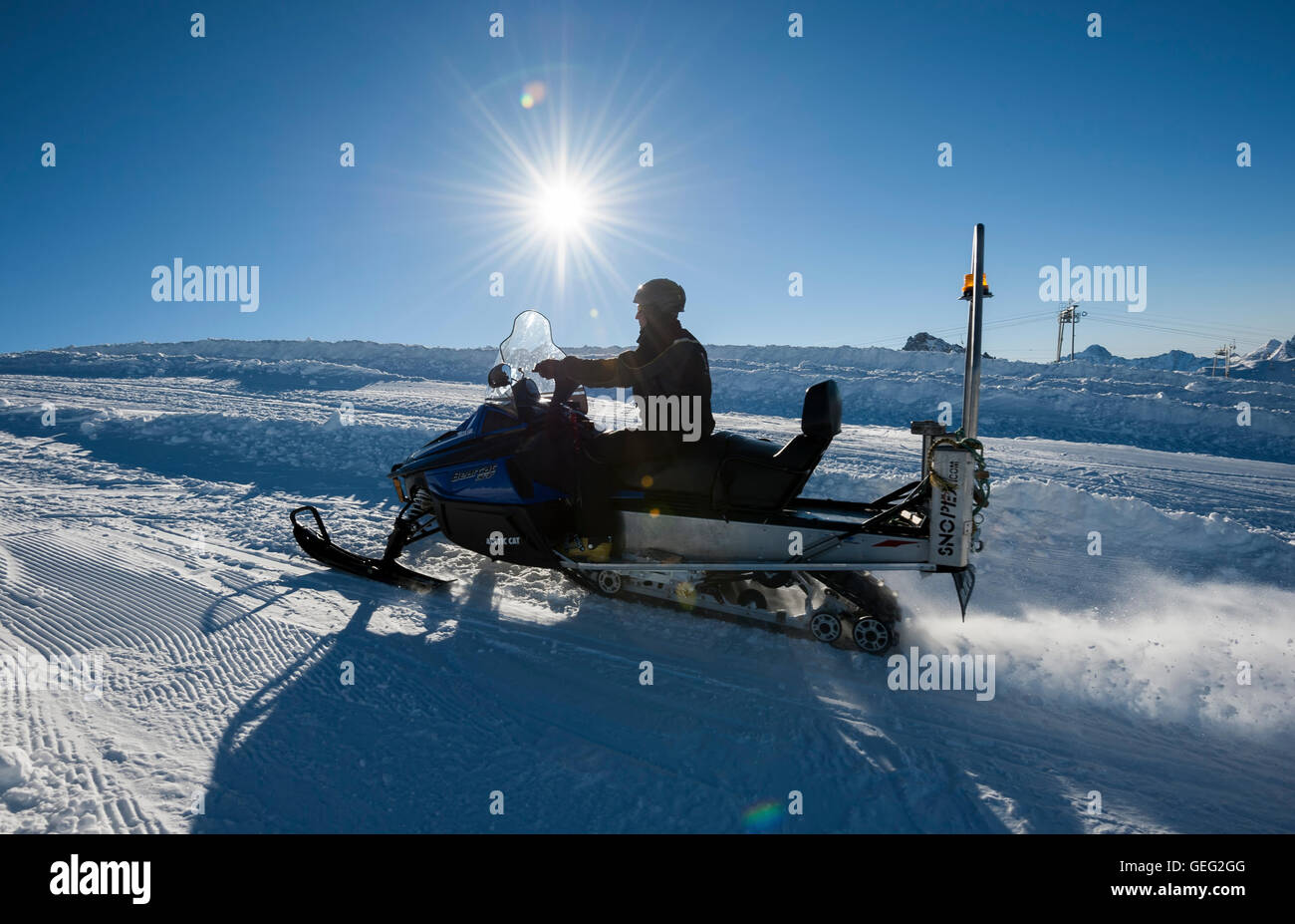 contre-jour shot of a men driving snowbike a and going to the Glacier, ski resort called 'les Deux Alpes'. - Stock Image