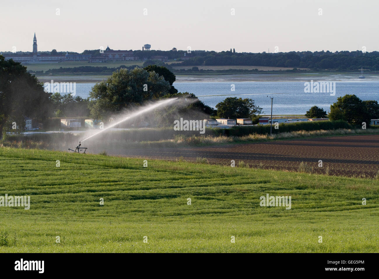 A field being irrigated by the River Stour and a caravan park with the Royal Hospital School in the background - Stock Image
