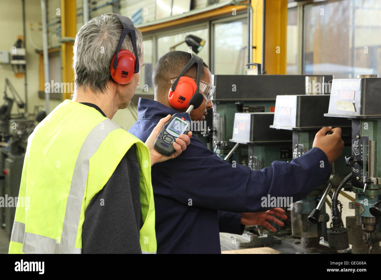 An environmental engineer monitors noise levels next to a drilling machine at a UK manufacturing plant - Stock Image