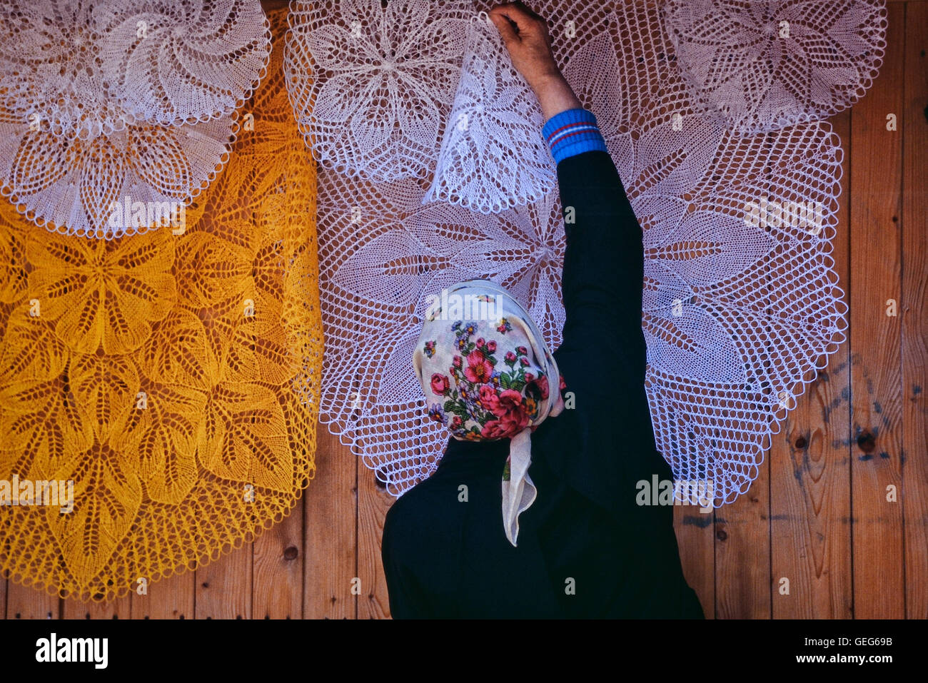 Stall holder hanging traditional lace tableclothes at the street market in Zakopane, Malopolskie Province, Poland - Stock Image