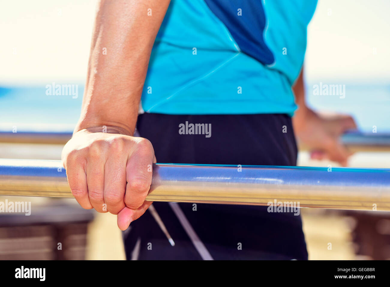 closeup of a young caucasian sportsman wearing sport clothes doing doing dips in parallel bars outdoors - Stock Image