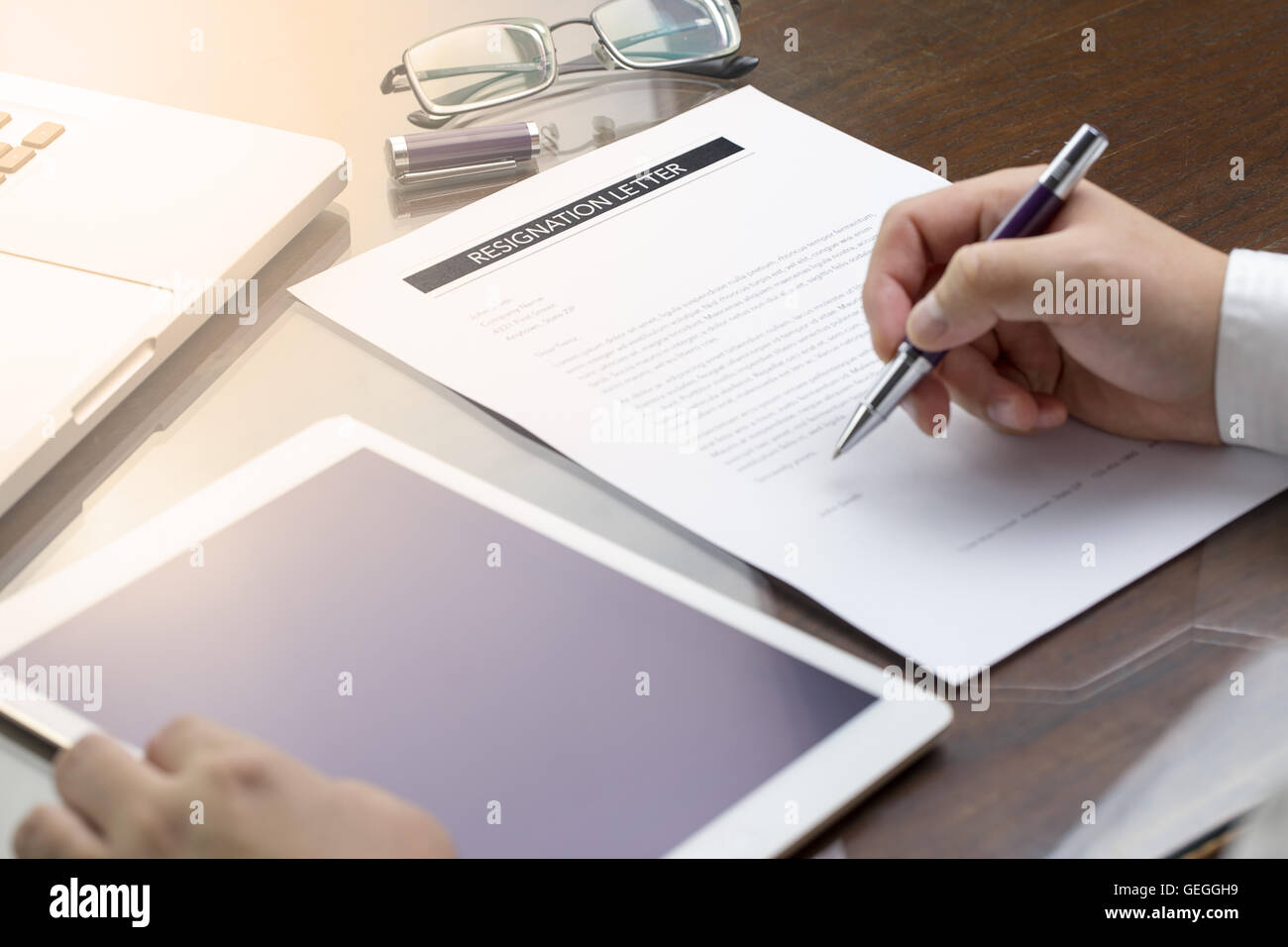 business man signing his resignation letter on his desk before stock