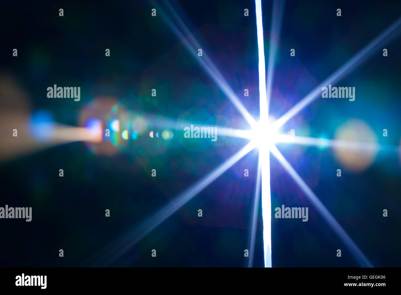 Real photographic lens flare of a bright light through a slit - Stock Image