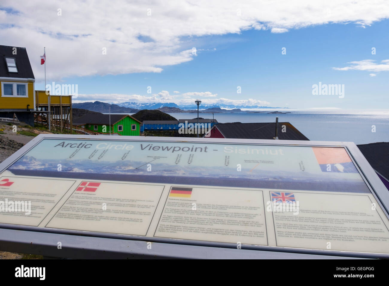 Multi-lingual information board at the Arctic Circle Viewpoint in summer with view south along coast. Sisimiut West Stock Photo
