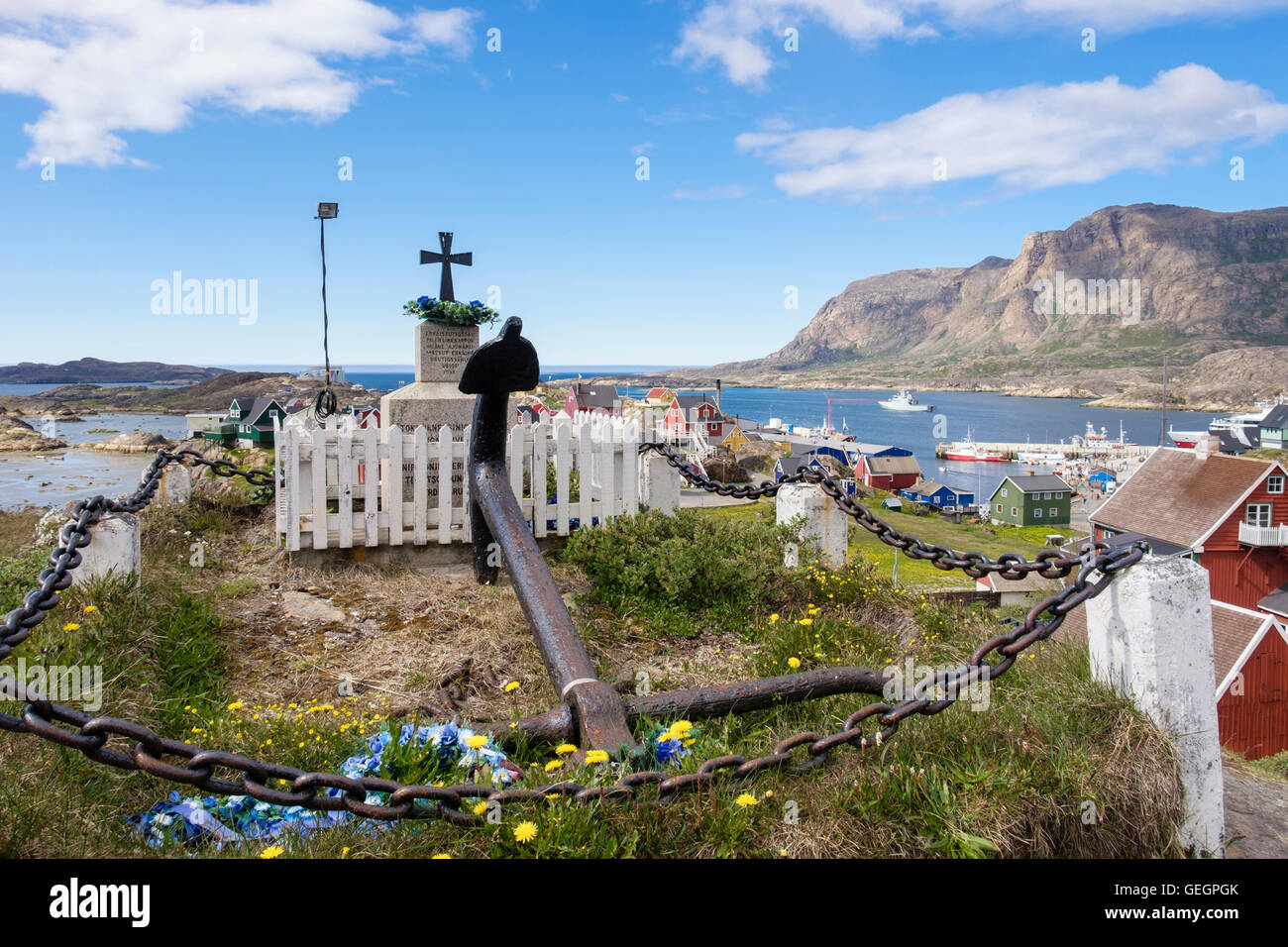 Anchor and crucifix memorial outside the new church with view to port on west coast in summer. Sisimiut Qeqqata Stock Photo