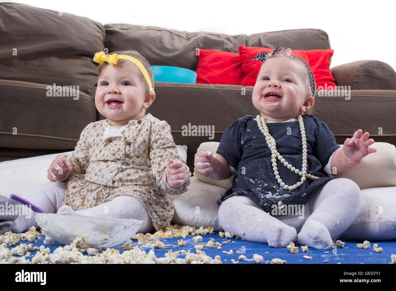 introducing food to baby, happy twin babies making a mess - Stock Image