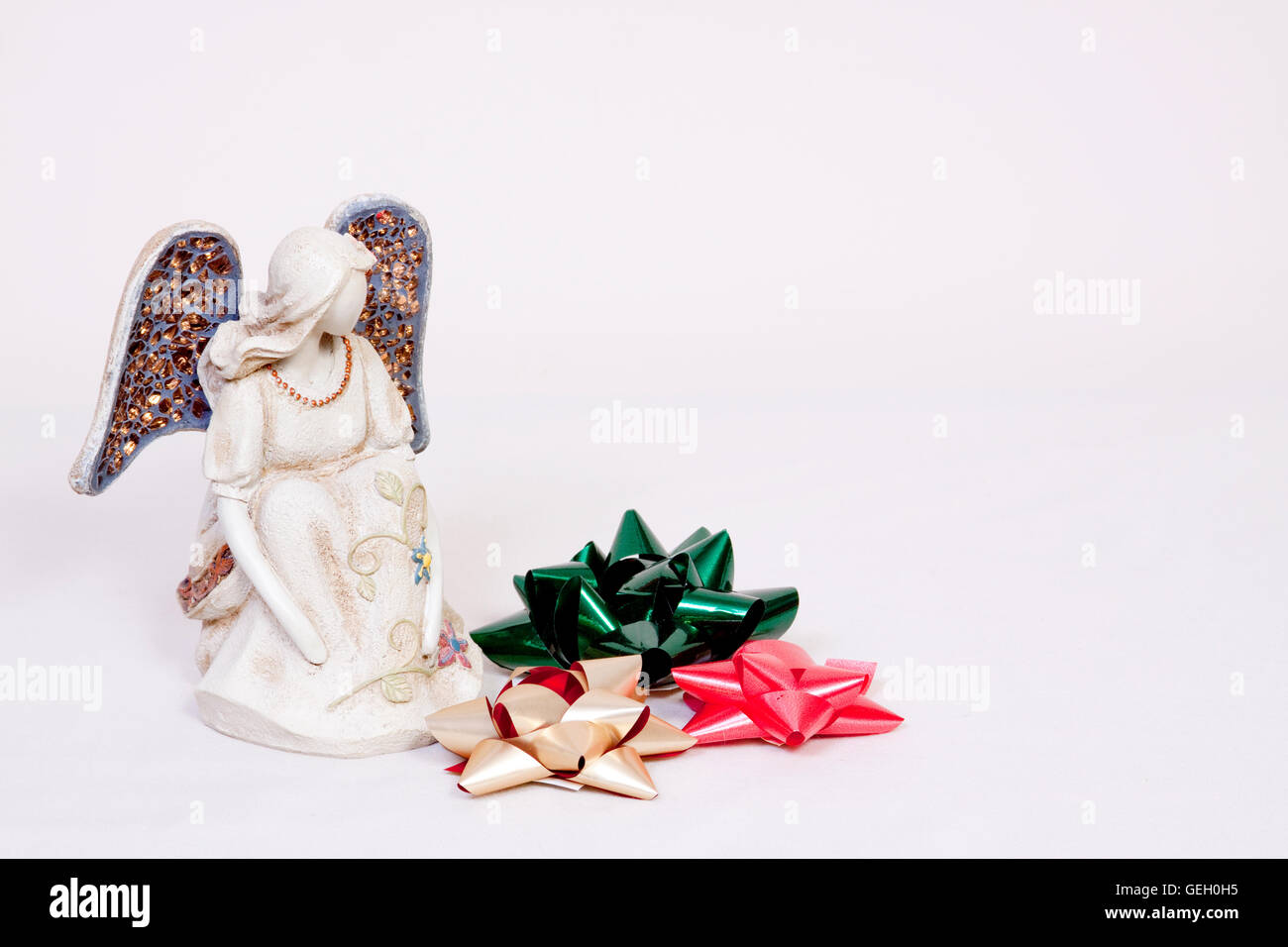 Angel with green, gold and red Christmas bows isolated - Stock Image