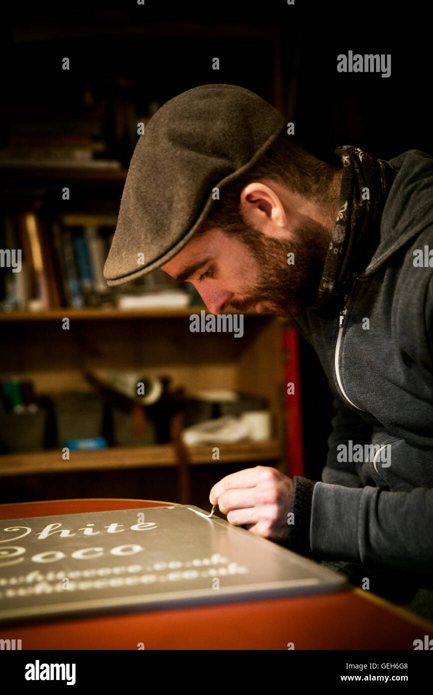 A sign writer working with a loaded brush painting a line freehand on the edge of a sign. - Stock Image