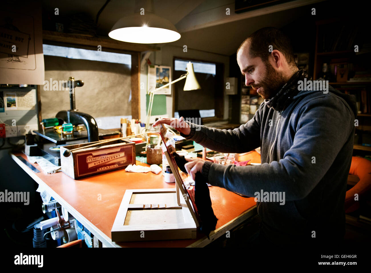 A sign writer at a workshop bench holding a sign. - Stock Image