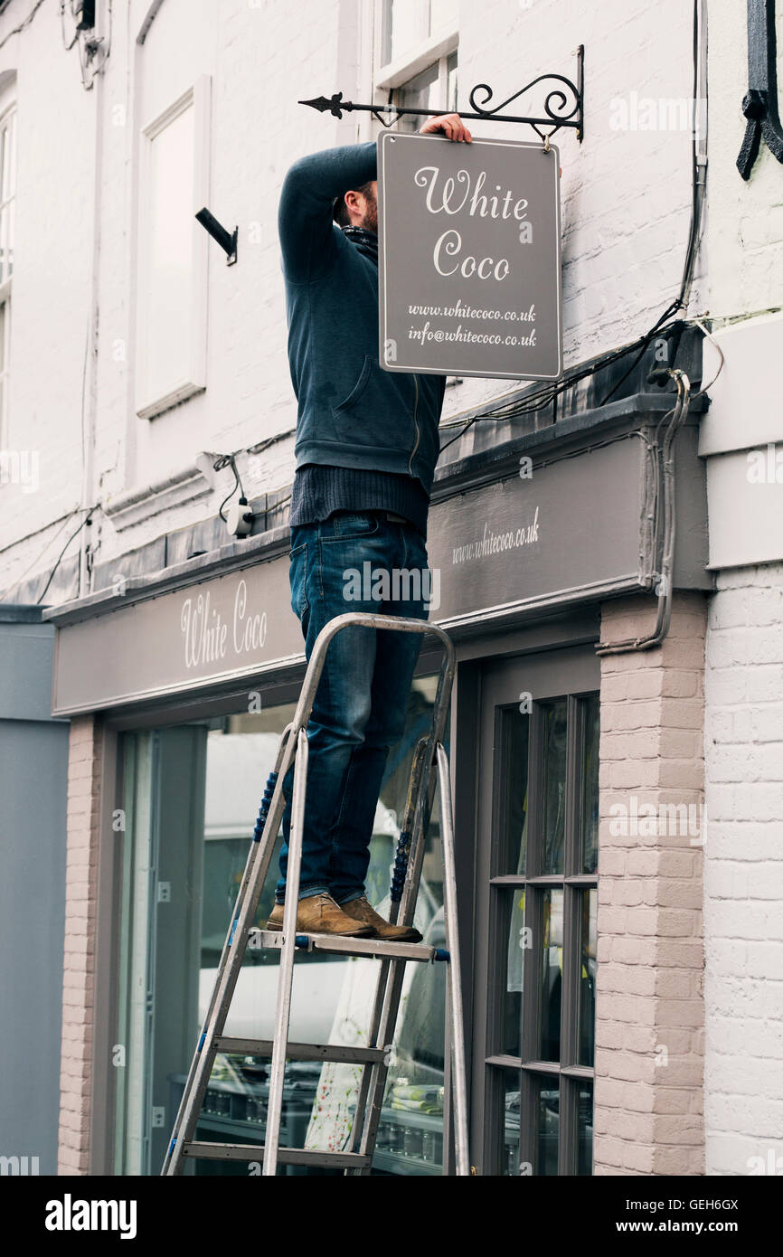 A man on a ladder fixing a painted name sign onto a bracket on a shopfront. - Stock Image