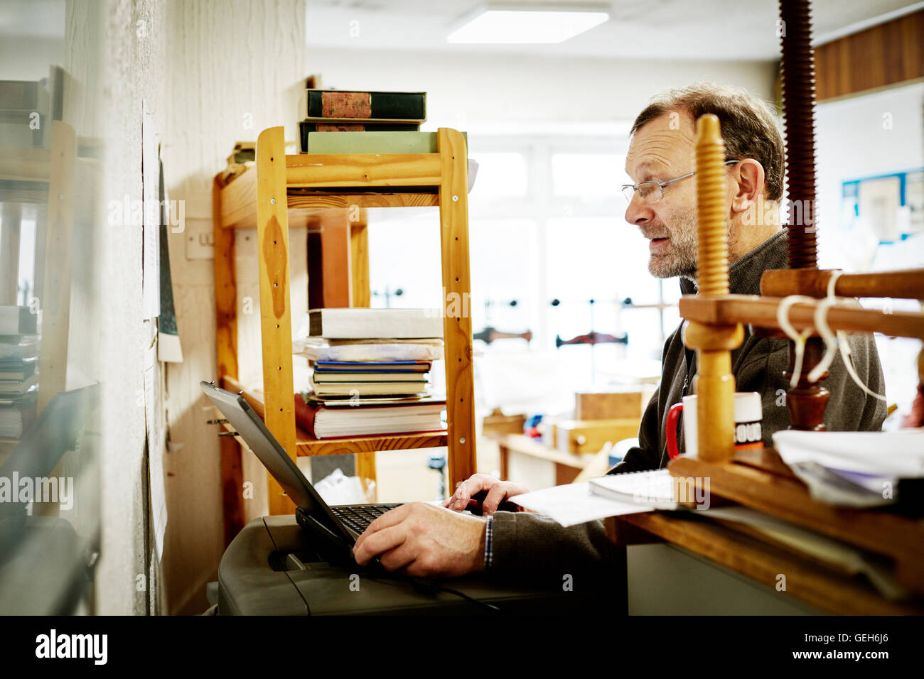 A man using a laptop computer on a bookbinding business. - Stock Image