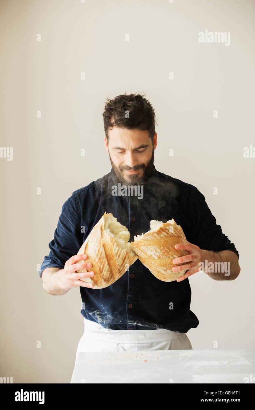 Baker holding two freshly baked loaves of bread. - Stock Image