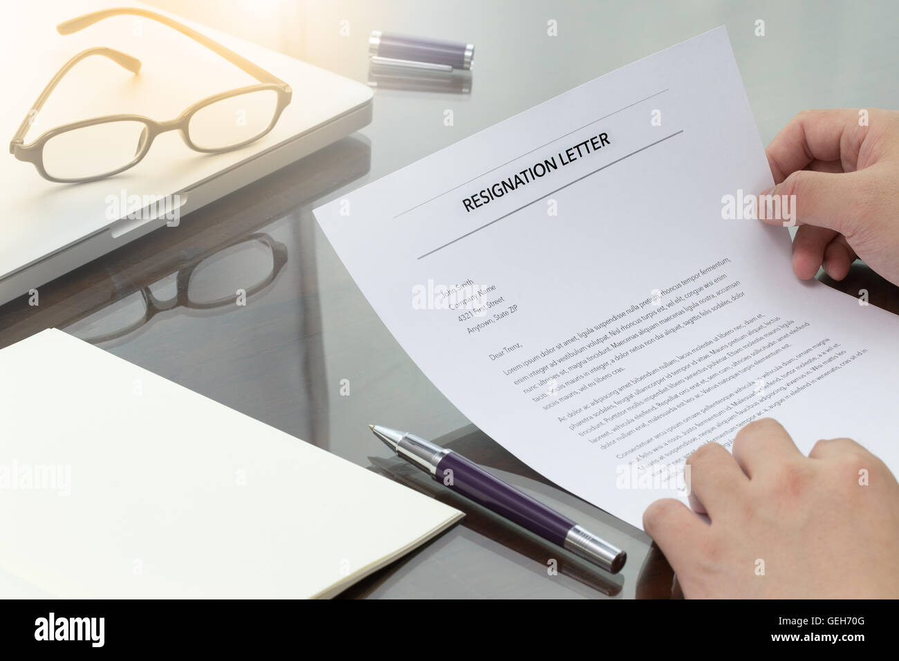 Businessman review his resignation letter on his desk before sending to his boss to quit his job. Resignation letter - Stock Image