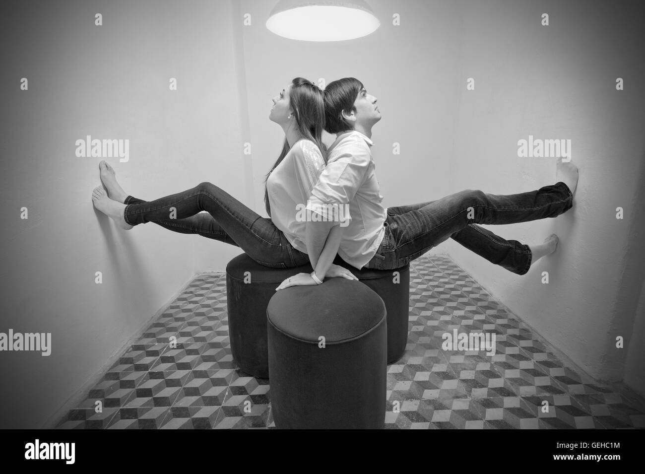 A young couple sit back to back with their feet against the wall in a confined space - Stock Image
