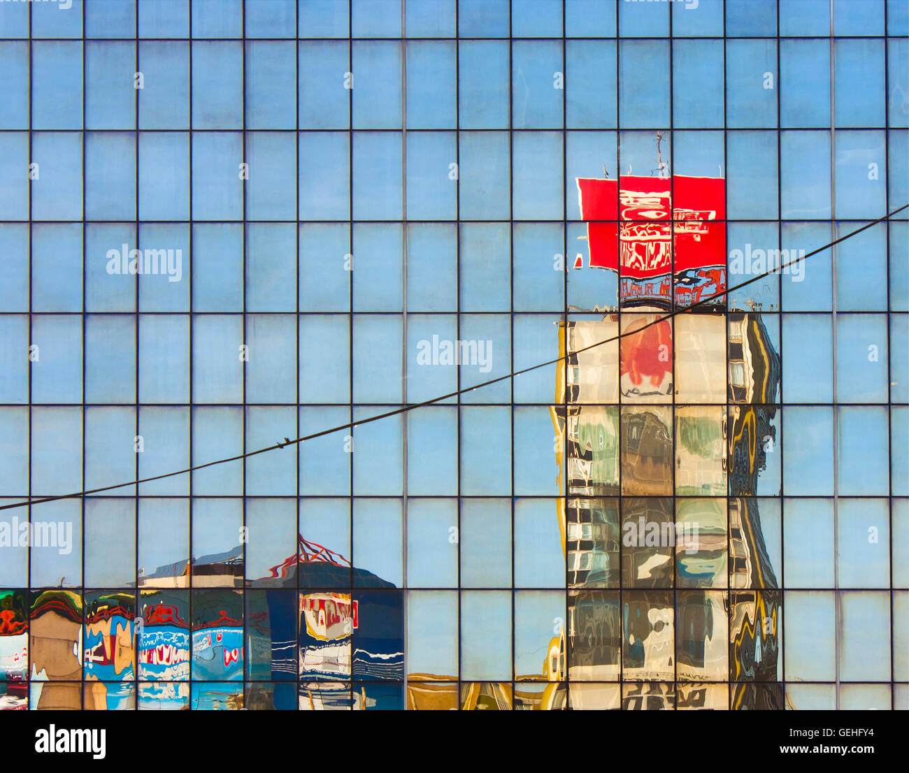City old buildings and skyscraper with billboards mirrored in a  glass building,  melting on a hot summer day - Stock Image